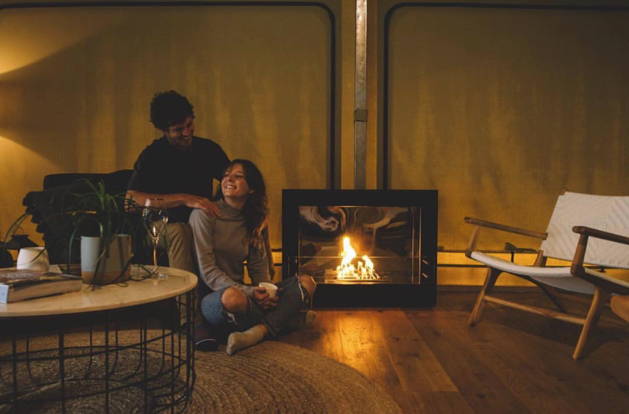 A couple sitting beside a fireplace